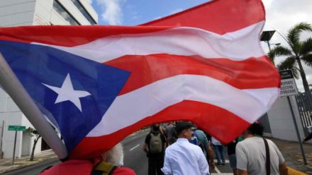 bandera puertorriqueña cargada por manifestante