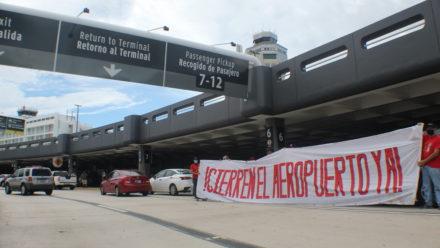 Caravana manifestación y pancarta grande diciendo Cierren el Aeropuerto Ya en el Aeropuerto Internacional