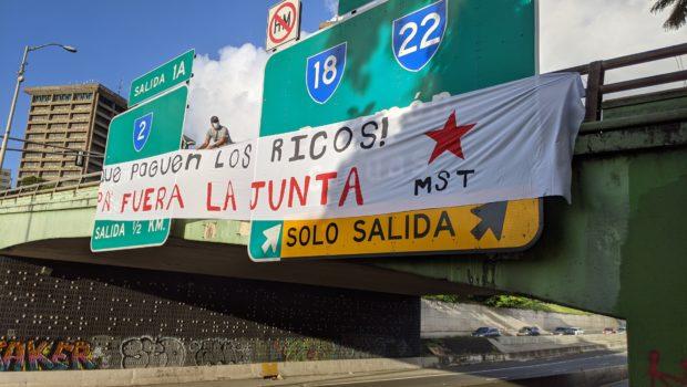 """Pancarta desplegada sobre expreso que lee: """"¡Que paguen los ricos! Pa' Fuera la Junta"""""""