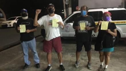 Foto de las cuatros personas arrestadas con citación en mano.