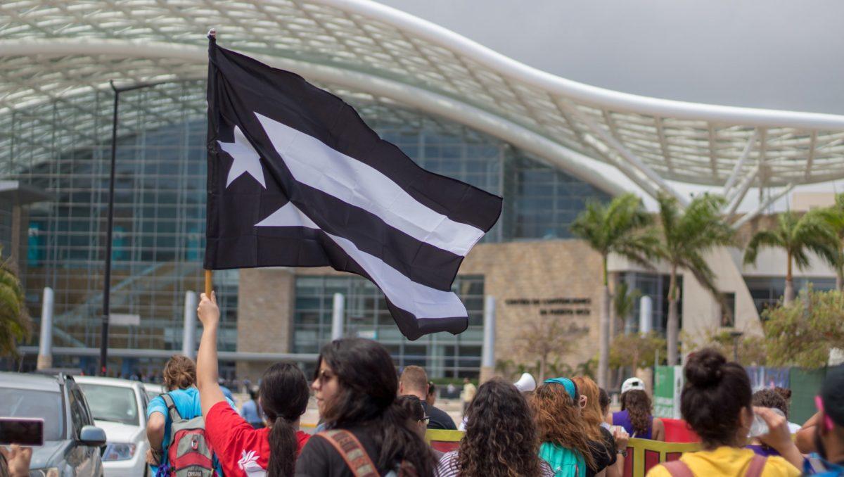 Bandera negra y blanca de Puerto Rico ondeando en una manifestación frente al Centr de Convenciones